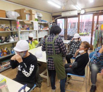訓練2:初動避難です。机の下に身を伏せてから、職員の指示に従いヘルメットの着用です。