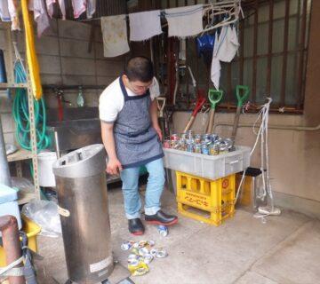 洗い終えたアルミ缶を足でつぶす作業の開始です。きれいに揃えて水切りをした後に、ひと缶づつ足でつぶしていきます。